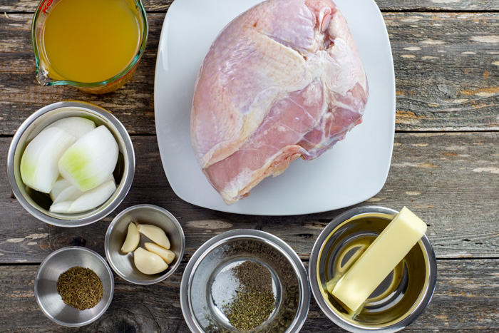 Instant pot turkey ingredients in bowls on a wooden surface: chicken broth, whole turkey, butter, seasonings, garlic, onion