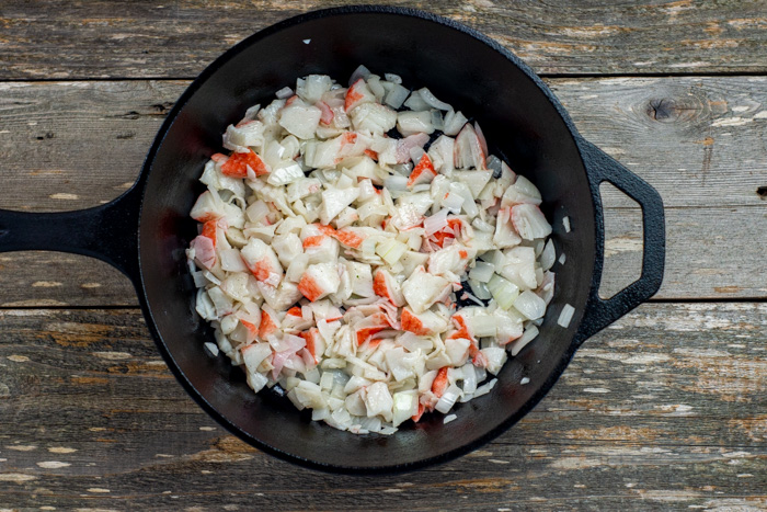 Diced onion and crab meat in butter in a cast iron skillet on a wooden surface