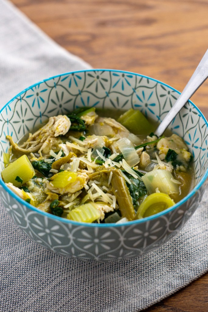 Green chicken soup garnished with parmesan cheese in a white and blue bowl with a stainless steel spoon on a grey placemat on a wooden surface (vertical)