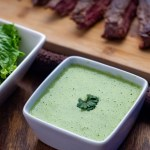 Green goddess dressing in a square white dish next to a larger square white bowl of salad and a bamboo tray with strips of meat behind all on a wooden surface (with title overlay)