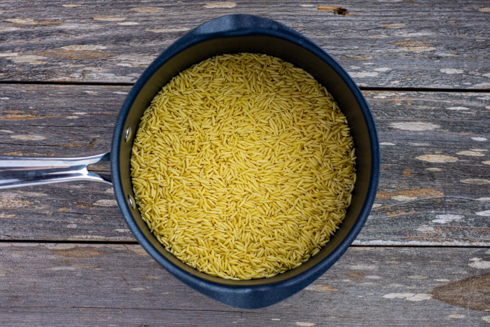 Uncooked orzo pasta in a saucepan on a wooden surface