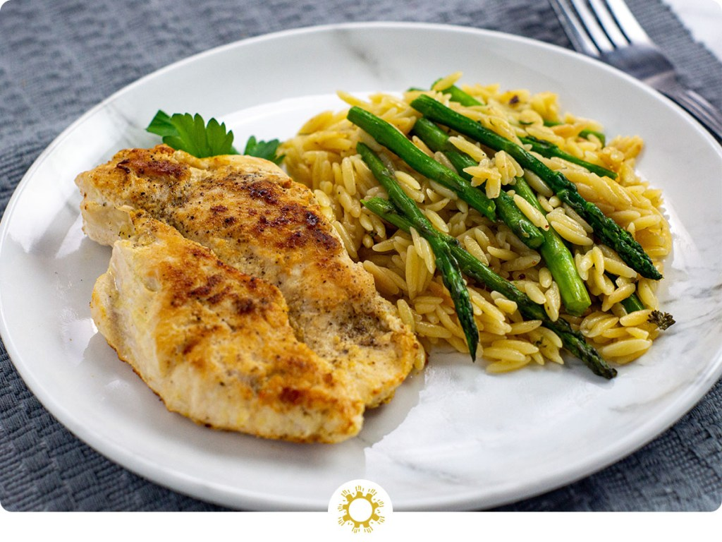 Honey Mustard Chicken with Orzo and asparagus on a white and grey marbled plate on top of a grey placemat (with logo overlay)
