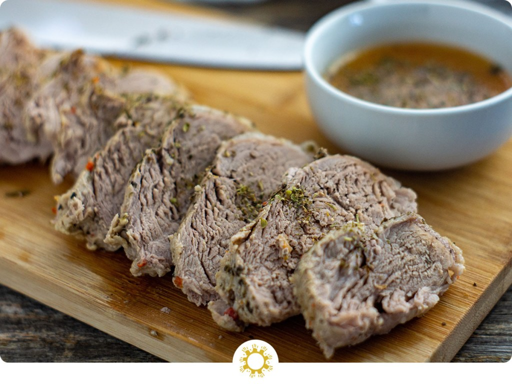 Instant Pot Pork Tenderloin sliced on a bamboo tray with dipping sauce in a round white bowl behind all on a wooden surface (with logo overlay)