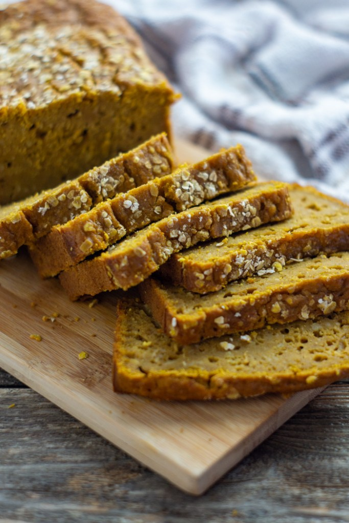 Sliced pumpkin maple bread on a bamboo tray with a white and brown towel behind all on a wooden surface (vertical)