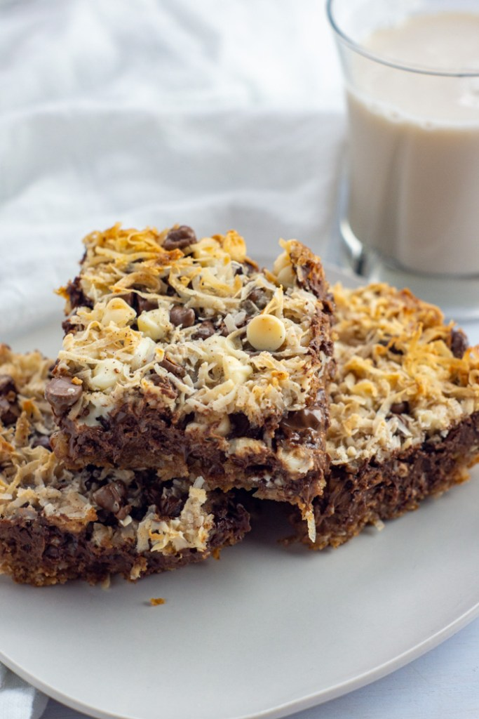 Three triple chocolate coconut bars on a square white plate with a cup of milk behind all on a white surface