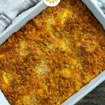 Yellow squash casserole in a white casserole dish with a white and brown towel behind all on a wooden surface (with title overlay)