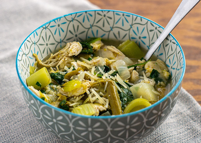 Green chicken soup garnished with parmesan cheese in a white and blue bowl with a stainless steel spoon on a grey placemat on a wooden surface