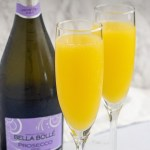 Two prosecco mimosa drinks in champagne flutes in front of a bottle of prosecco with a white towel behind all on a white surface (with title overlay)