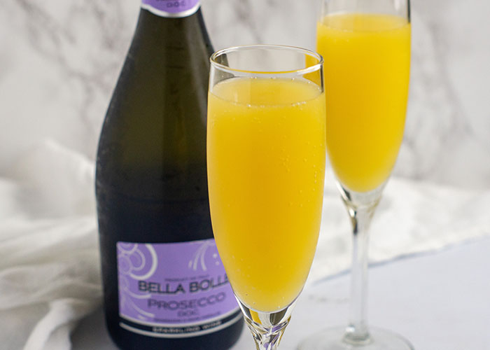 Two prosecco mimosa drinks in champagne flutes in front of a bottle of prosecco with a white towel behind all on a white surface