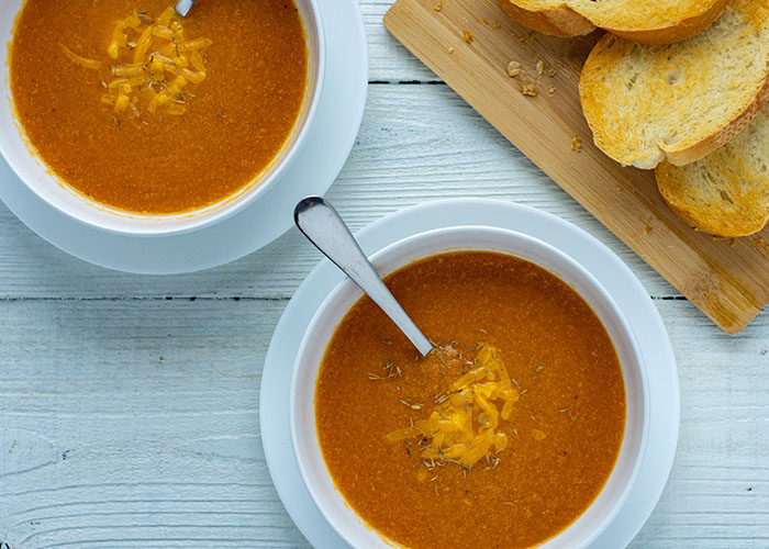 Roasted Tomato and Cheddar Soup in a round white bowl on a round white plate next to another bowl of soup and toasted bread on a bamboo board all on a white wooden surface