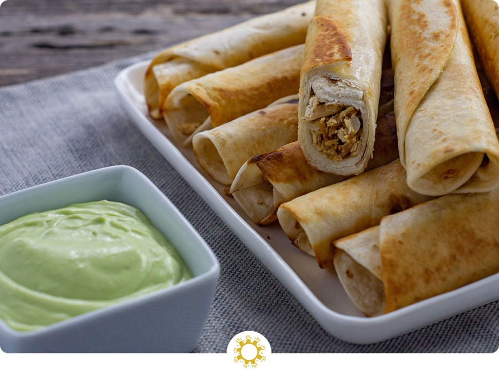 Chicken flautas piled on a square white platter next to a small square white dish with buttermilk avocado sauce on a grey placemat all on a wooden surface (with logo overlay)