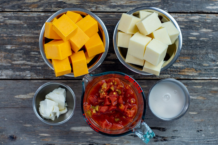 Ingredients for homemade queso in stainless steel bowls on a wooden surface