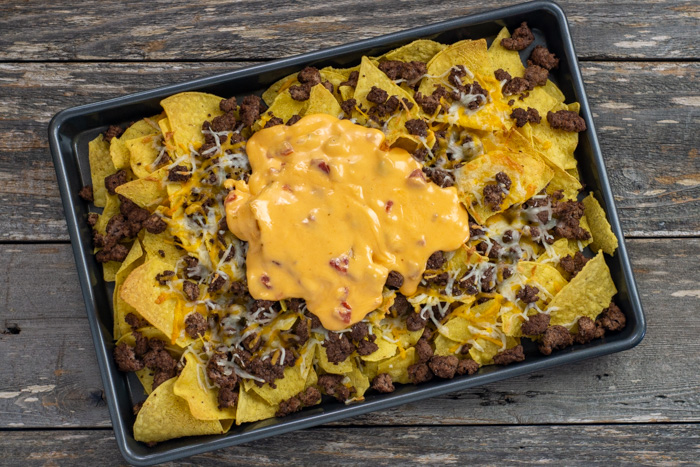 Tortilla chips covered with ground beef, melted shredded cheese and queso on a metal baking sheet on a wooden surface