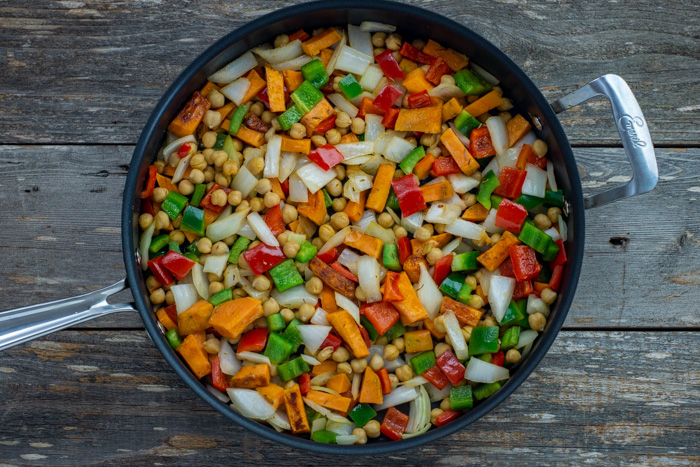 Diced sweet potato, onion, bell peppers, and chickpeas in a skillet over a wooden surface