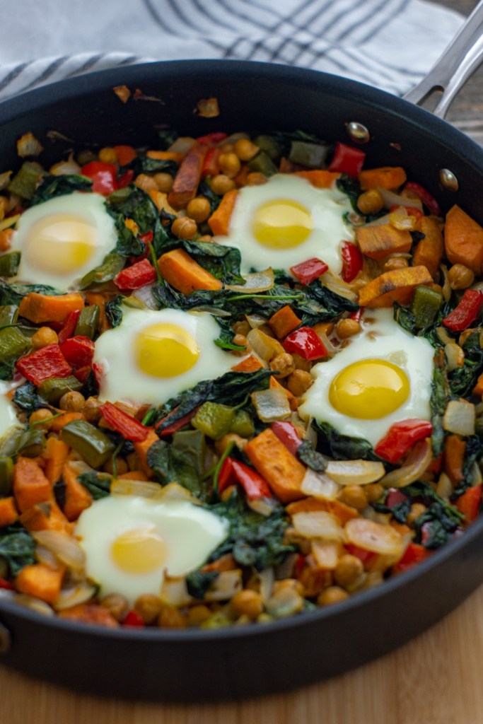 Healthy breakfast hash of sweet potatoes, chickpeas, bell peppers, onion, spinach, and eggs in a skillet on a bamboo cutting board with a white and grey towel behind all on a wooden surface (vertical)