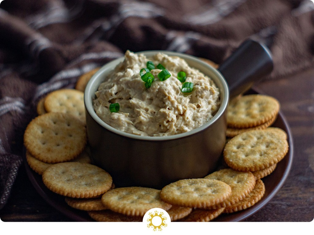 Hot crab dip topped with sliced green onion in a round brown bowl surrounded by Ritz crackers on a brown plate with a brown and white towel behind (with logo overlay)