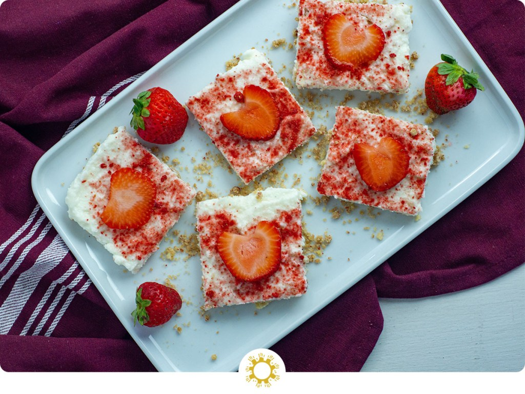 White chocolate strawberry dessert bars with whole strawberries and dried strawberry powder on a long white dish on top of a red and white placemat on a white surface (with logo overlay)