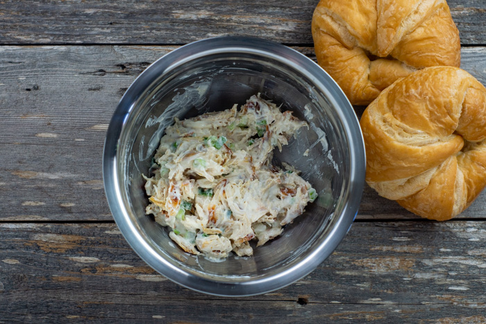 Chicken salad mixture in a stainless steel bowl next to croissant rolls on a wooden surface