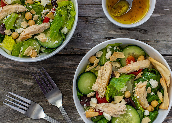 Two bowls of Greek chicken salad next to a smaller bowl of dressing with a spoon and a fork next to the bowls all on a wooden surface