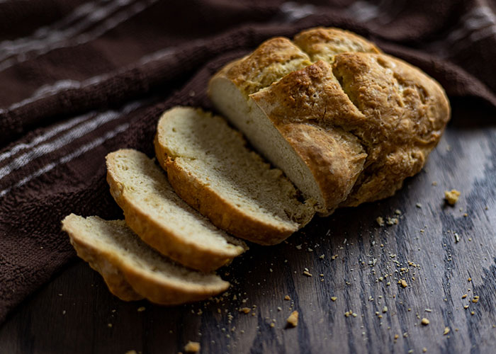 Irish Soda Bread with a few slices cut off with a brown and white towel behind all on a wooden surface