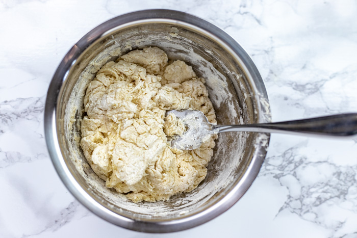 Dough for soda bread in a stainless steel bowl with a wire whisk on a white and grey marble surface