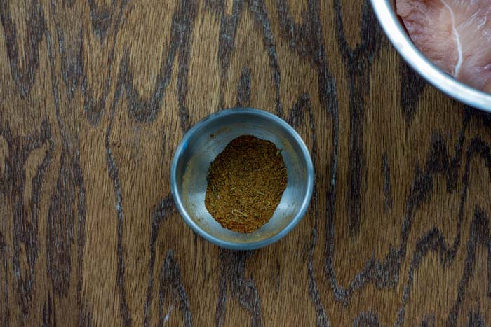 Seasonings in a small stainless steel bowl on a wooden surface