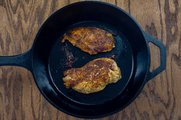 Browned chicken in a cast-iron skillet on a wooden surface