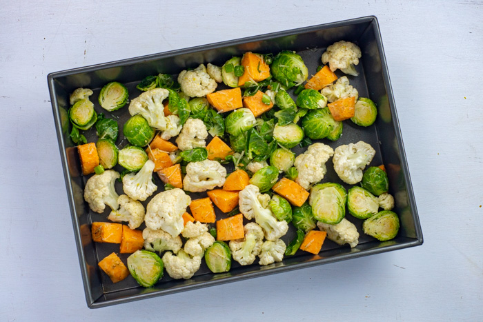 Coated raw vegetables spread out on a baking pan on a white surface