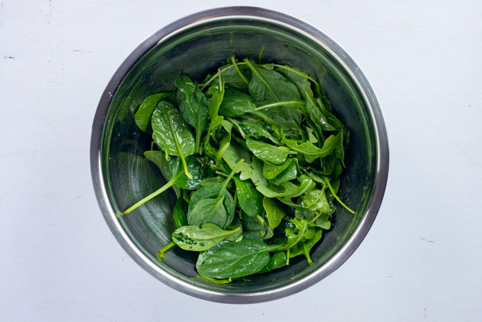 Spinach and arugula tossed with dressing in a stainless steel bowl on a white surface