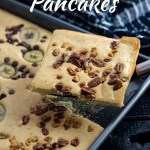 Piece of sheet pan pancakes being lifted on a spatula over the pan of pancakes with a black and white towel behind (with title overlay)