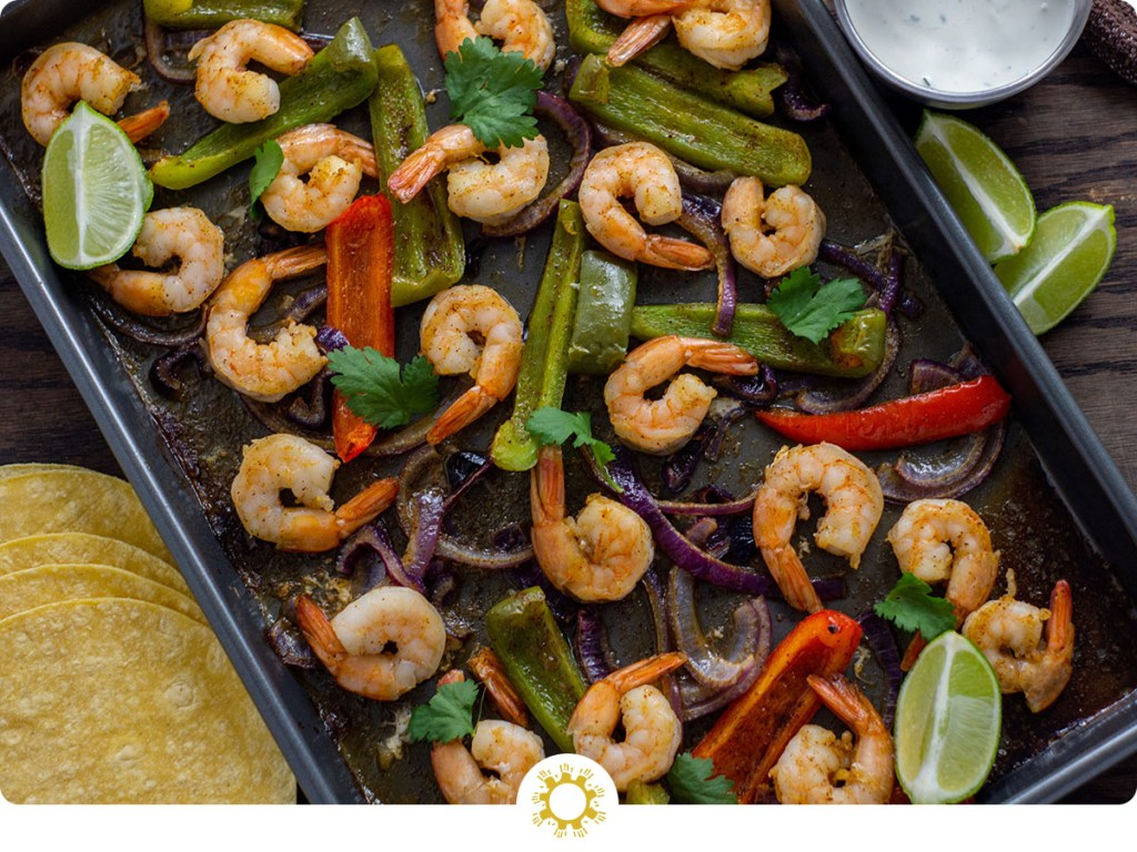 Shrimp and roasted vegetables for shrimp fajitas on a metal baking sheet next to a stainless steel bowl of sour cream sauce with lime wedges and corn tortillas to the side and a brown towel behind all on a wooden surface (with logo overlay)