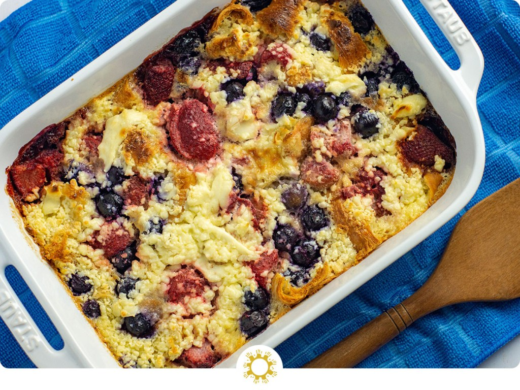 Berry croissant bake in a white casserole dish next to a wooden spoon on a blue towel (with logo overlay)