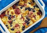 Berry croissant bake in a white casserole dish next to a wooden spoon on a blue towel