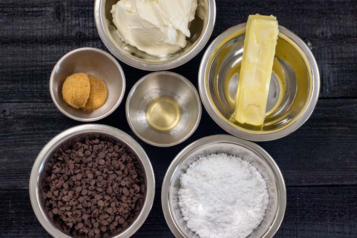 Ingredients for cookies and cream dip in stainless steel bowls on a dark wooden surface