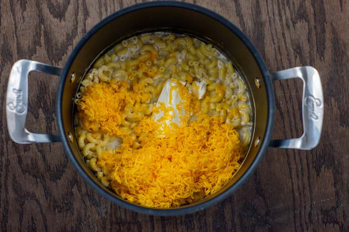 Cooked macaroni noodles topped with cheese in a stockpot on a wooden surface