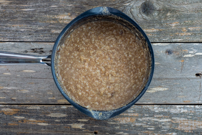 Cooked oats in a saucepan on a wooden surface