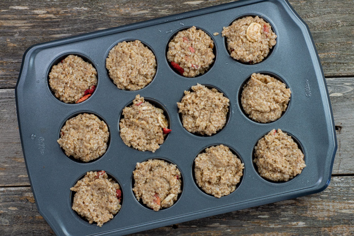 Cooked oatmeal scooped into muffin cups on a wooden surface