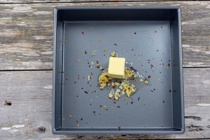 Butter and seasonings in a square metal baking dish on a wooden surface