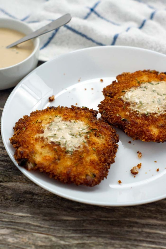 Two salmon cakes topped with buttermilk sauce on a round white plate with a bowl of buttermilk sauce and a white and blue towel behind all on a wooden surface (vertical)