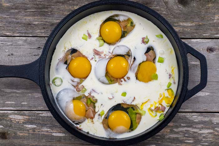 Diced ham and leeks with eggs and heavy cream in a cast iron skillet on a wooden surface