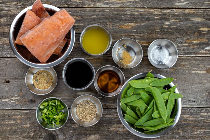 Ingredients for orange ginger salmon in stainless steel bowls on a wooden surface