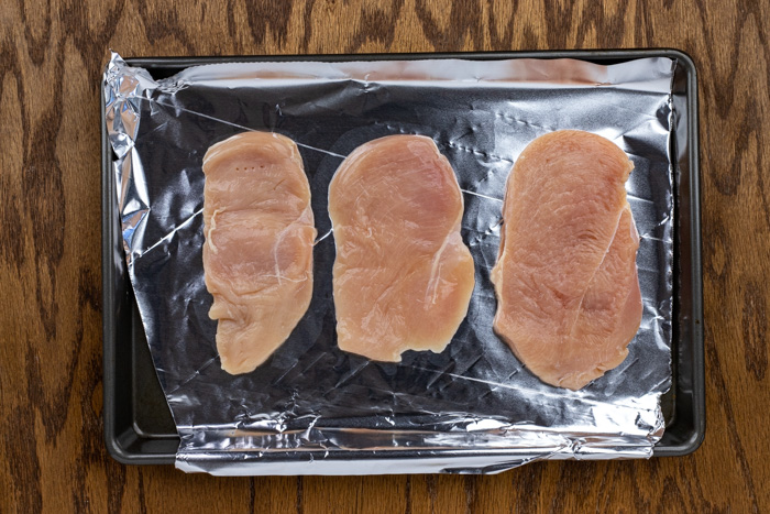 Raw chicken breast on a baking sheet covered with aluminum foil on a wooden surface