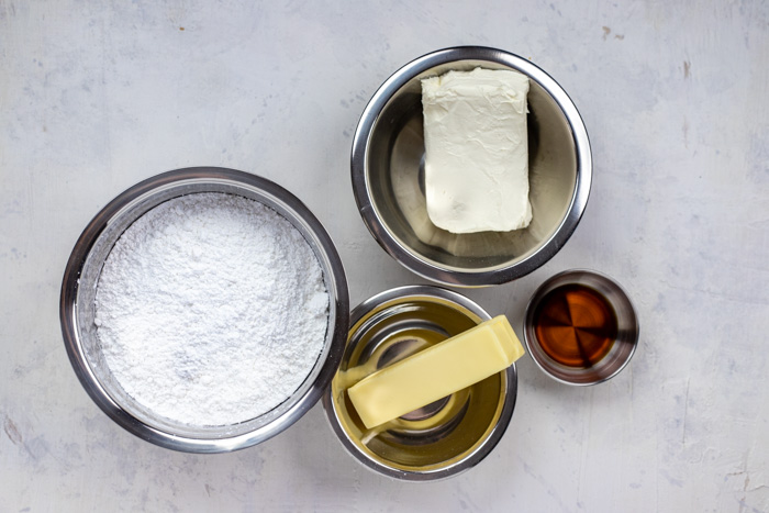 Frosting ingredients in stainless steel bowls on a white wooden surface