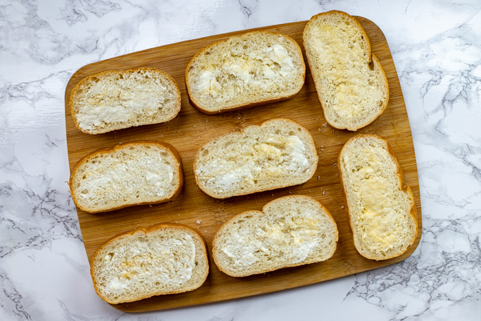 Sliced bread covered with butter and garlic powder on a bamboo tray on a white and grey marbled surface