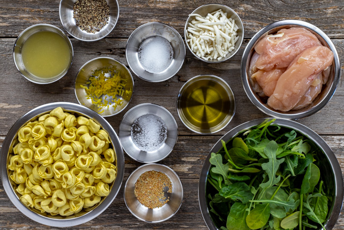 Ingredients for chicken tortellini salad in stainless steel bowls on a wooden surface