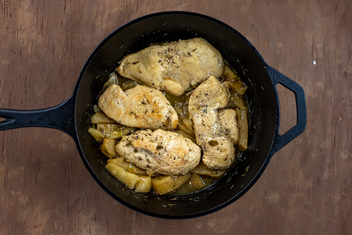Cooked apples with chicken in a cast-iron skillet on a wooden surface