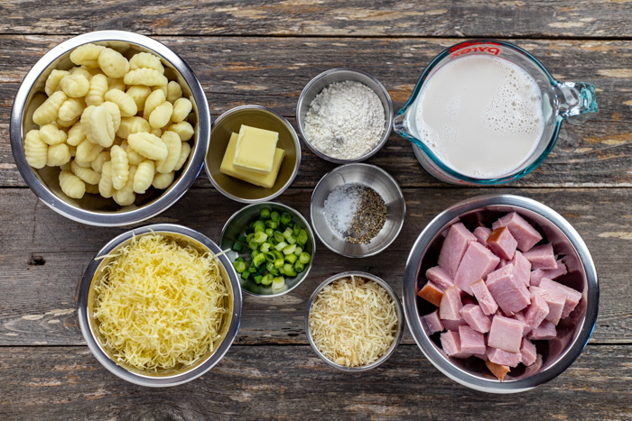 Ingredients for ham steak and gnocchi casserole in stainless steel bowls on a wooden surface