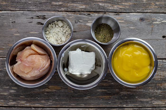 Ingredients for slow cooker creamy ranch chicken in stainless steel bowls on a wooden surface