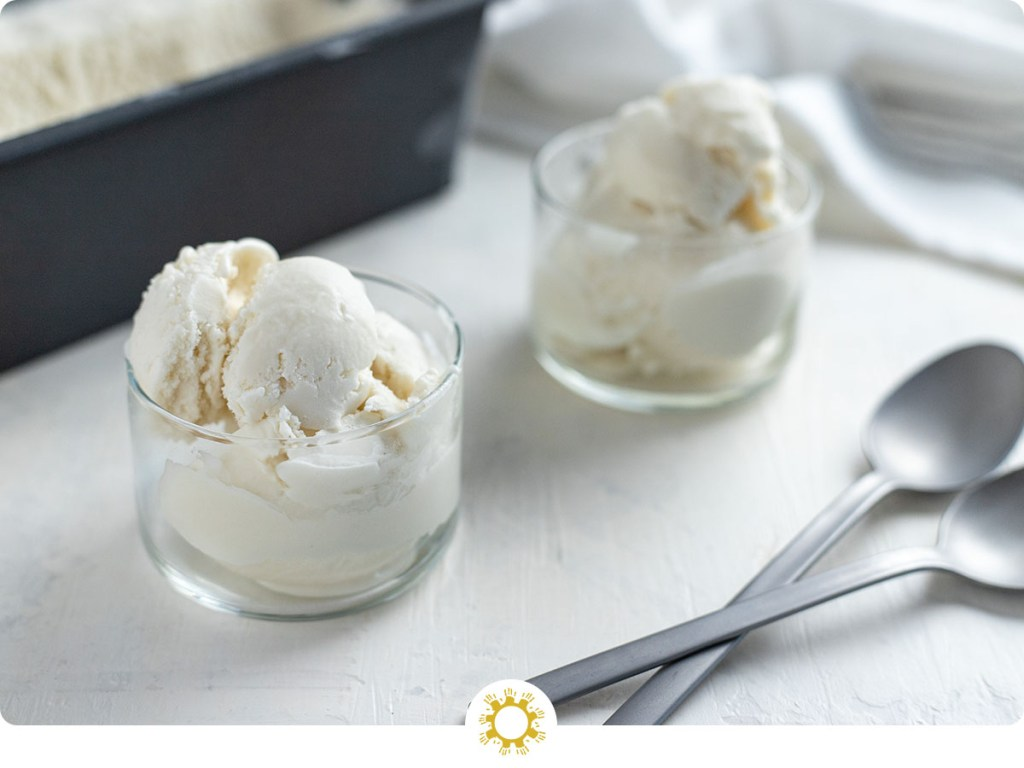 Vegan coconut ice cream in a small glass dish with another serving and a loaf pan of ice cream behind next to stainless steel spoons all on a white and grey surface (with logo overlay)