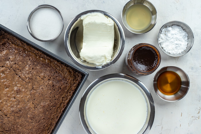 Ingredients for brownie cheesecake trifle in stainless steel bowls on a white surface